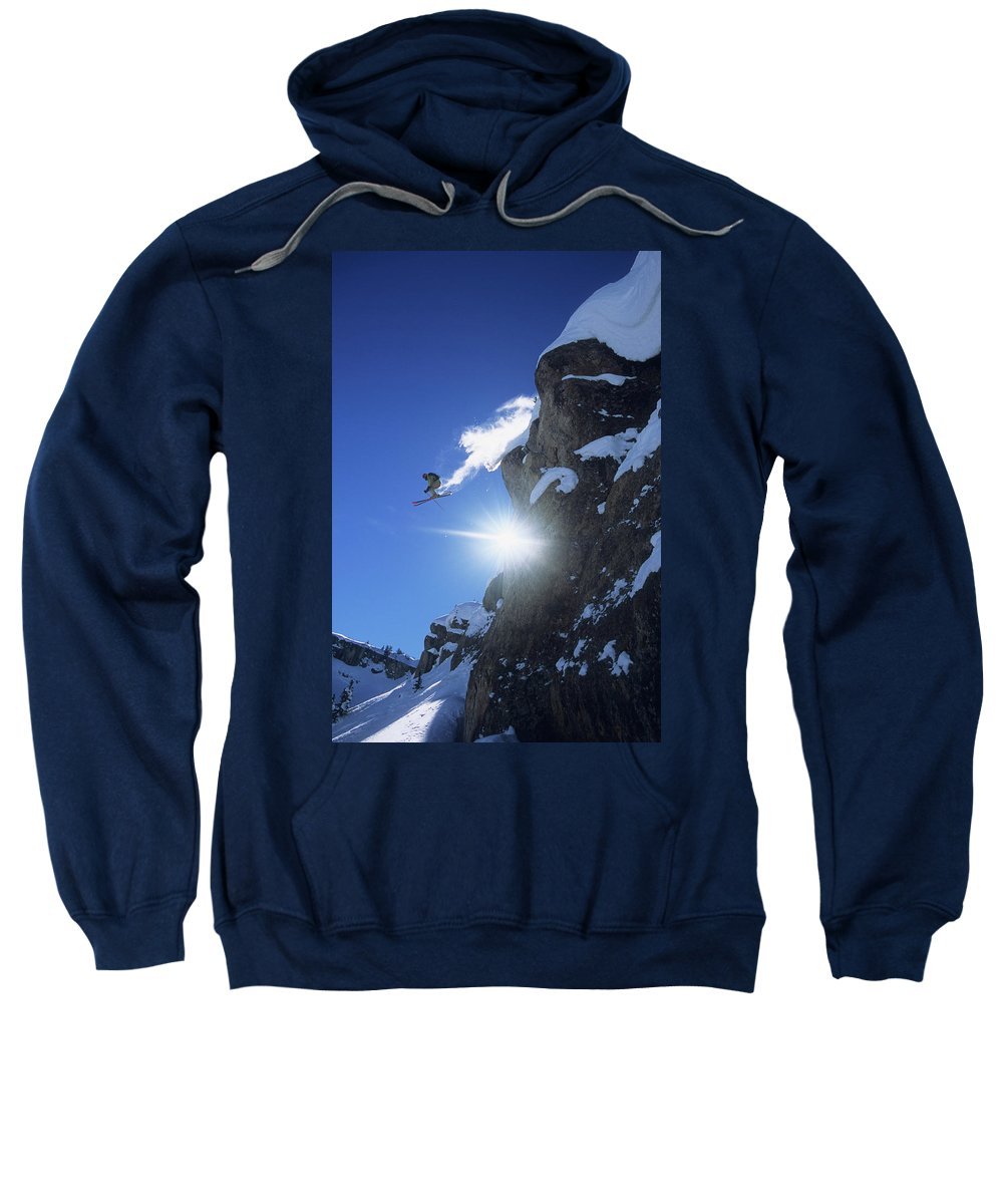 Adventure Sweatshirt featuring the photograph An Extreme Skier Jumps Off A Snowy by Jeff Diener