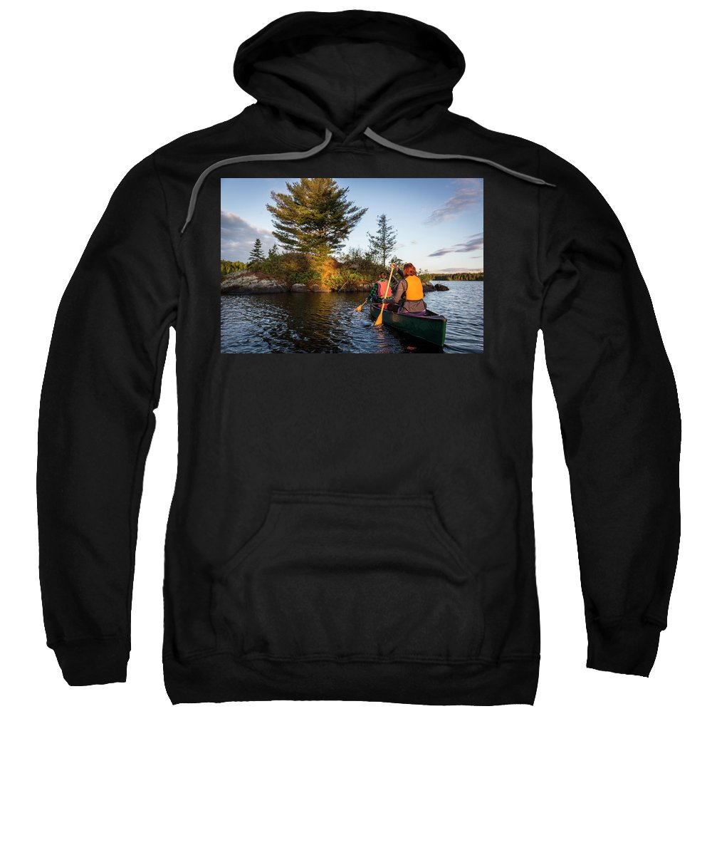 Pond Sweatshirt featuring the photograph A Young Couple Paddles A Canoe On Long by Jerry Monkman
