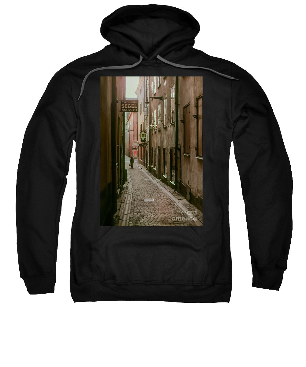 Woman Women Sign Signs Cobblestone Street Streets Cobblestones City Cities Cityscape Cityscapes Building Buildings Structure Structures Architecture Creature Creatures Door Doors Window Windows People Person Persons Stockholm Sweden Sweatshirt featuring the photograph A Lonely Walk Home by Bob Phillips