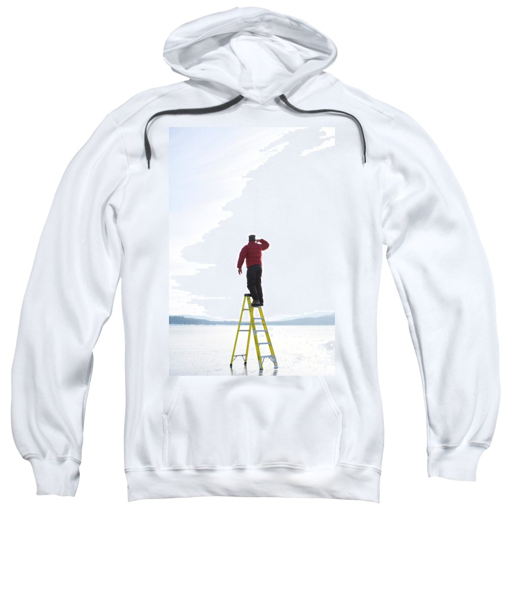 Arm Raised Sweatshirt featuring the photograph Man Atop Ladder On A Frozen Lake by Woods Wheatcroft