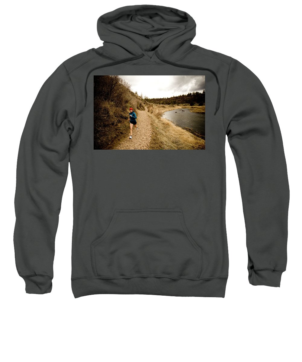 25-29 Years Sweatshirt featuring the photograph A Woman Jogging On A Dirt Trail by Jordan Siemens