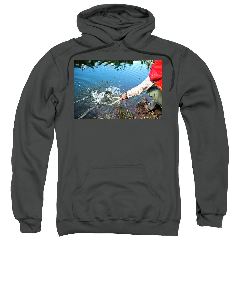 Human Hand Sweatshirt featuring the photograph A Fly Fisherman Pulls A Fish by Rob Hammer