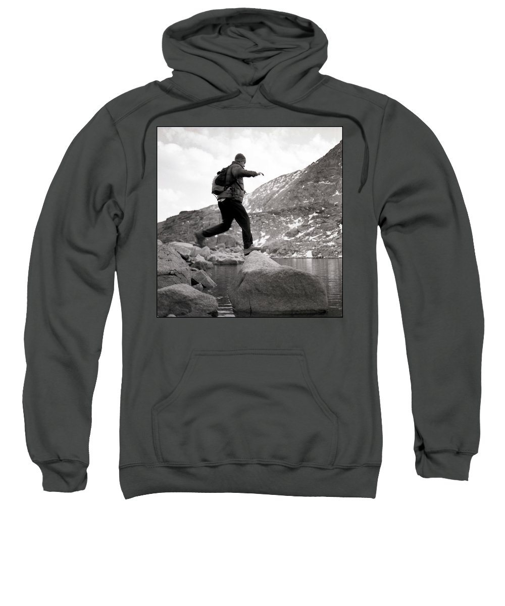 Alone Sweatshirt featuring the photograph A Man Jumps From One Rock To Another by Michael Hanson