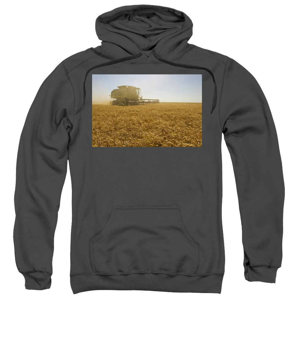 Canadian Sweatshirt featuring the photograph A Combine Harvester Works A Field by Dave Reede