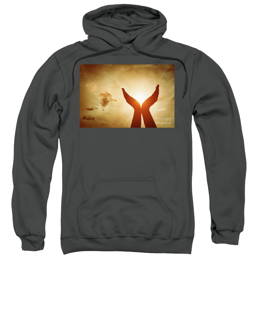 Hands Sweatshirt featuring the photograph Raised Hands Catching Sun On Sunset Sky. Concept Of Spirituality, Wellbeing, Positive Energy by Michal Bednarek