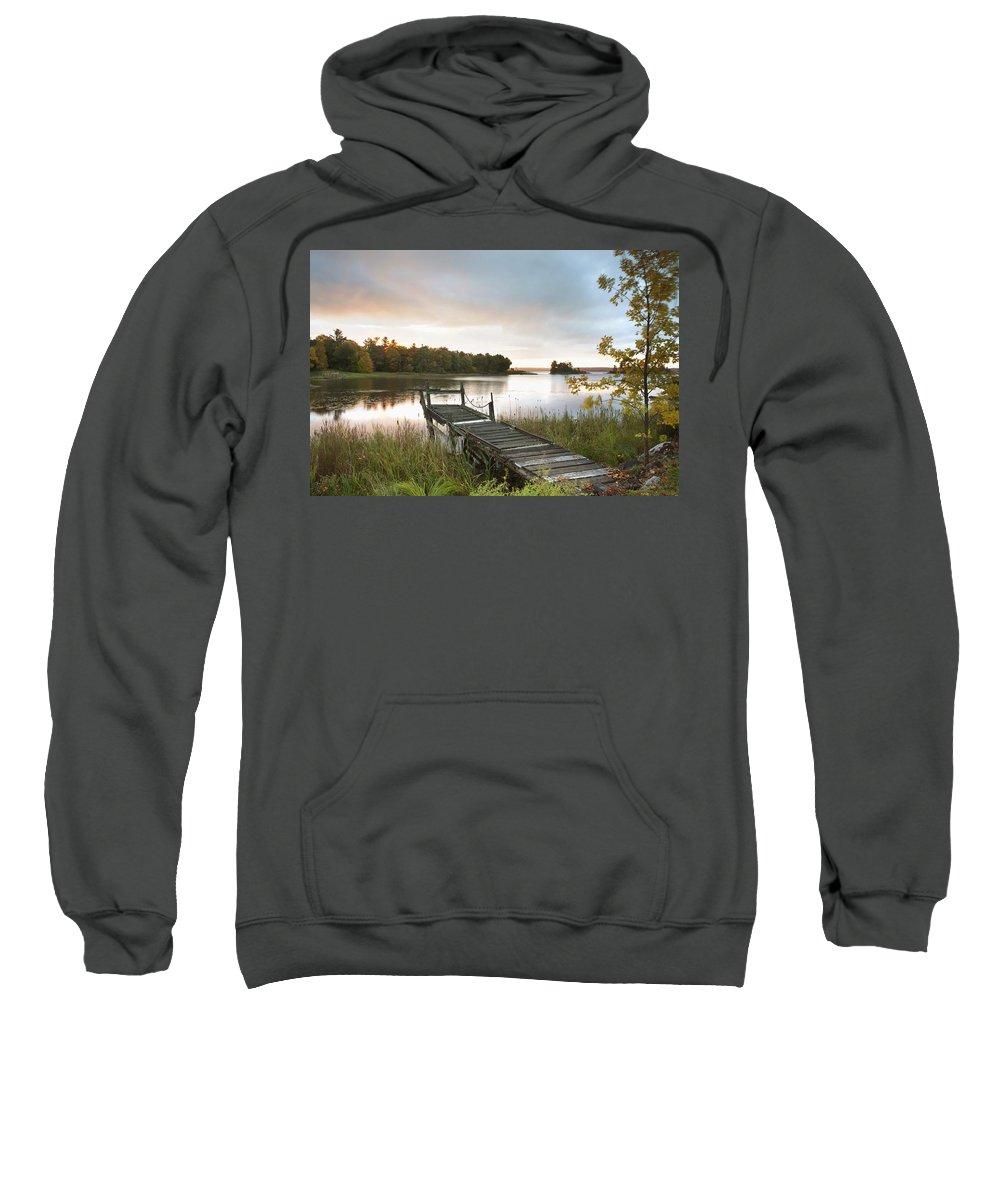 Sunrise Sweatshirt featuring the photograph A Dock On A Lake At Sunrise Near Wawa by Susan Dykstra
