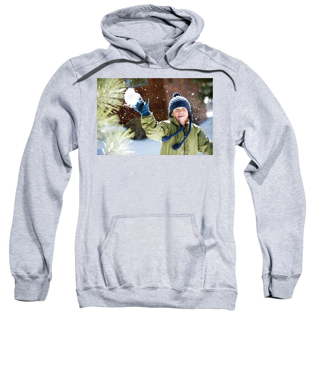 8-9 Years Sweatshirt featuring the photograph A Boy Throws A Snowball While Playing by Corey Rich