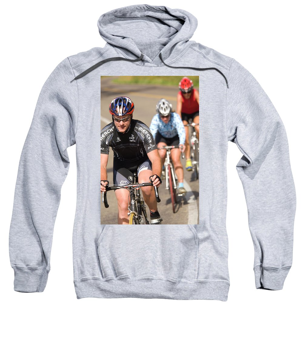 Action Sweatshirt featuring the photograph Cyclists Climb A Hill With A Mountain by Heath Korvola