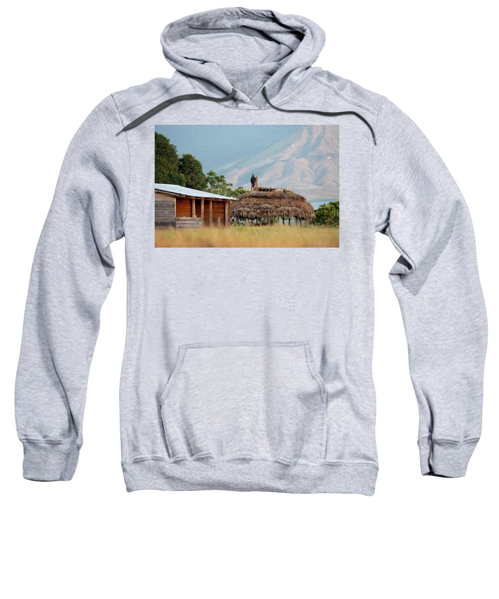 People Sweatshirt featuring the photograph A Man Repairs His Roof With Branches by Jeanlouis Wertz