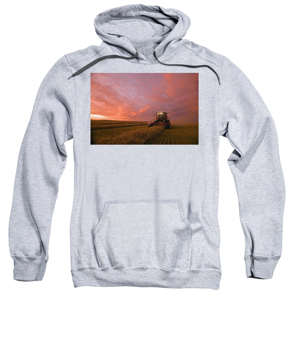 Canadian Sweatshirt featuring the photograph Farmer Harvesting Oat Crop by Dave Reede