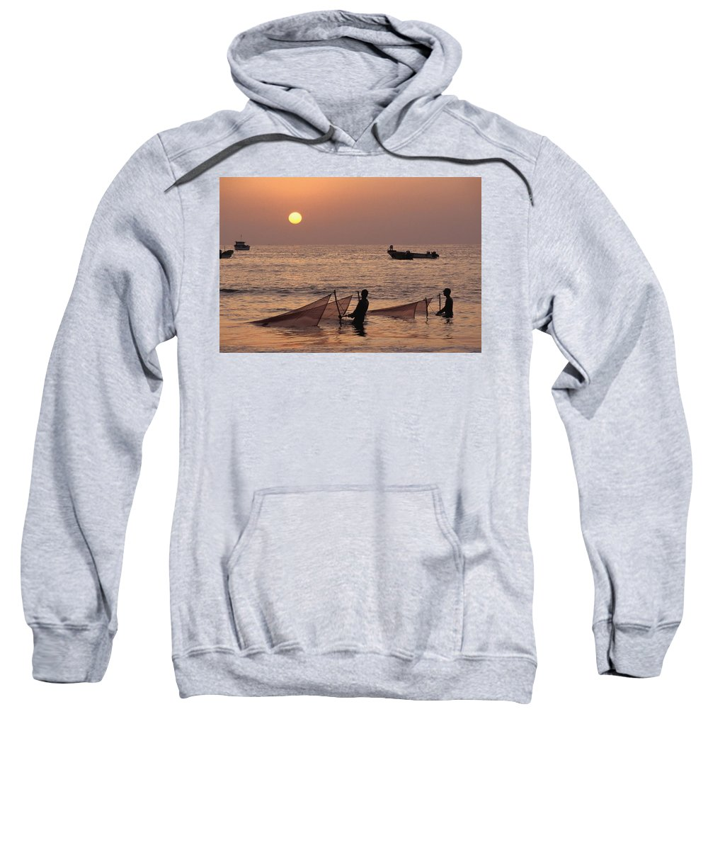 Photography Sweatshirt featuring the photograph Fishermen Holding Nets In Sea At Sunset by Axiom Photographic