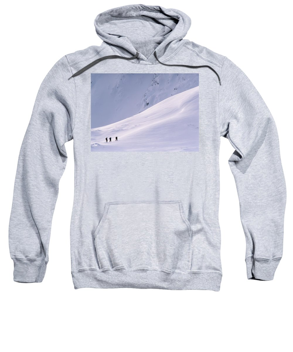 Winter Sweatshirt featuring the photograph Three Hikers Walking Up A Snow Covered by Axiom Photographic