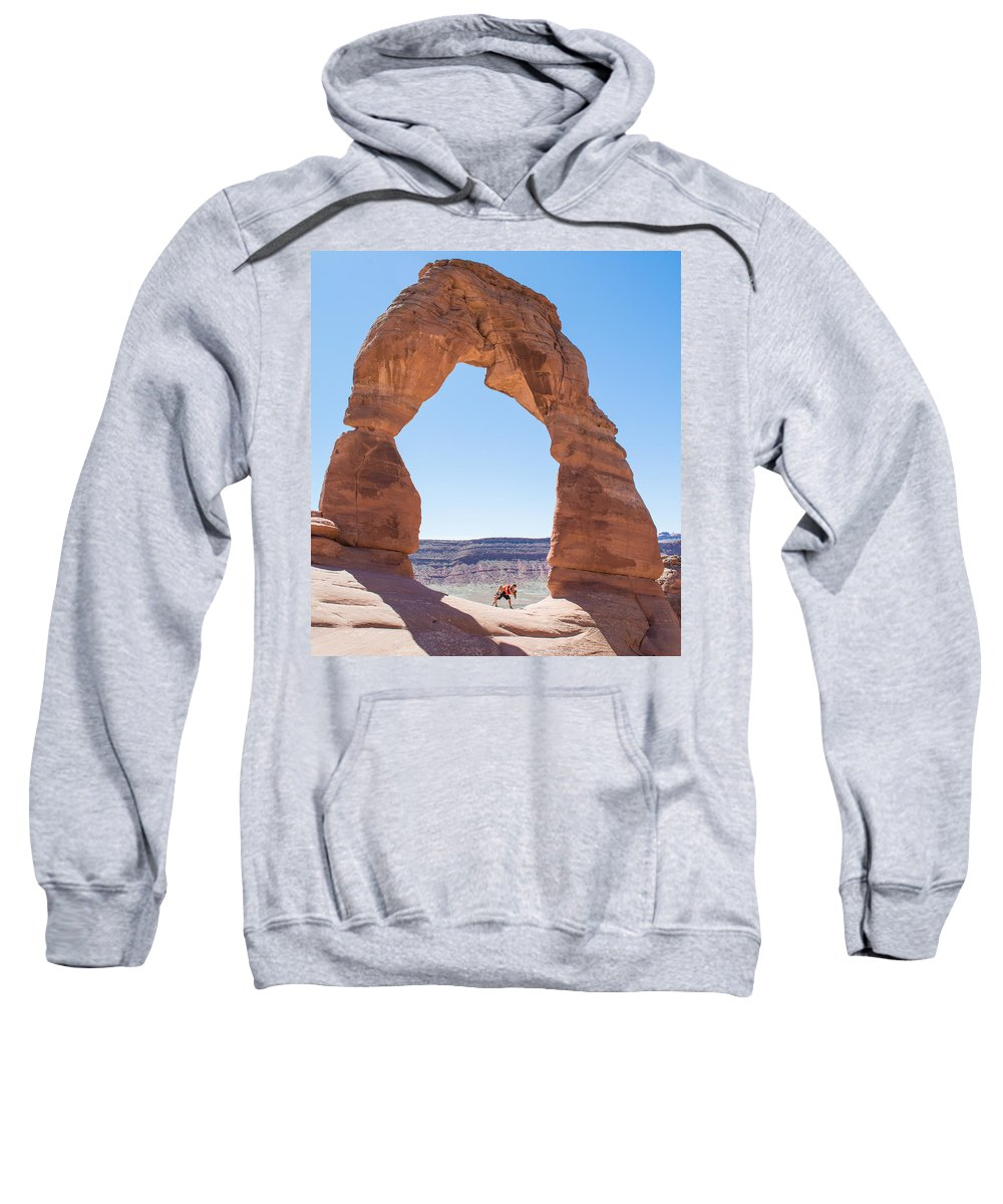 Arch Sweatshirt featuring the photograph A Couple Kissing Under Delicate Arch In The Arches National Par by Elijah Weber