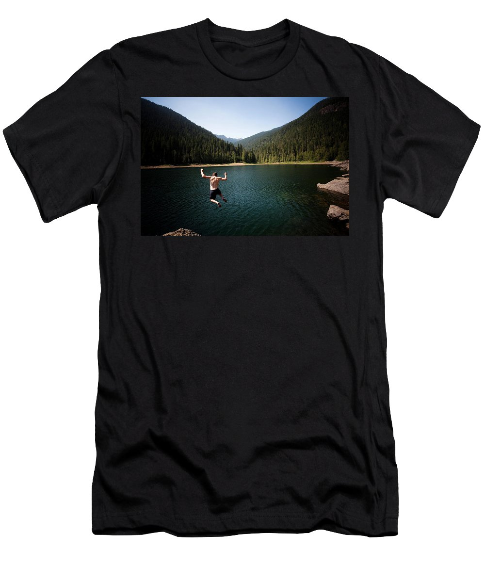 20s Men's T-Shirt (Athletic Fit) featuring the photograph A Young Man Jumps From A Ledge by Michael Hanson