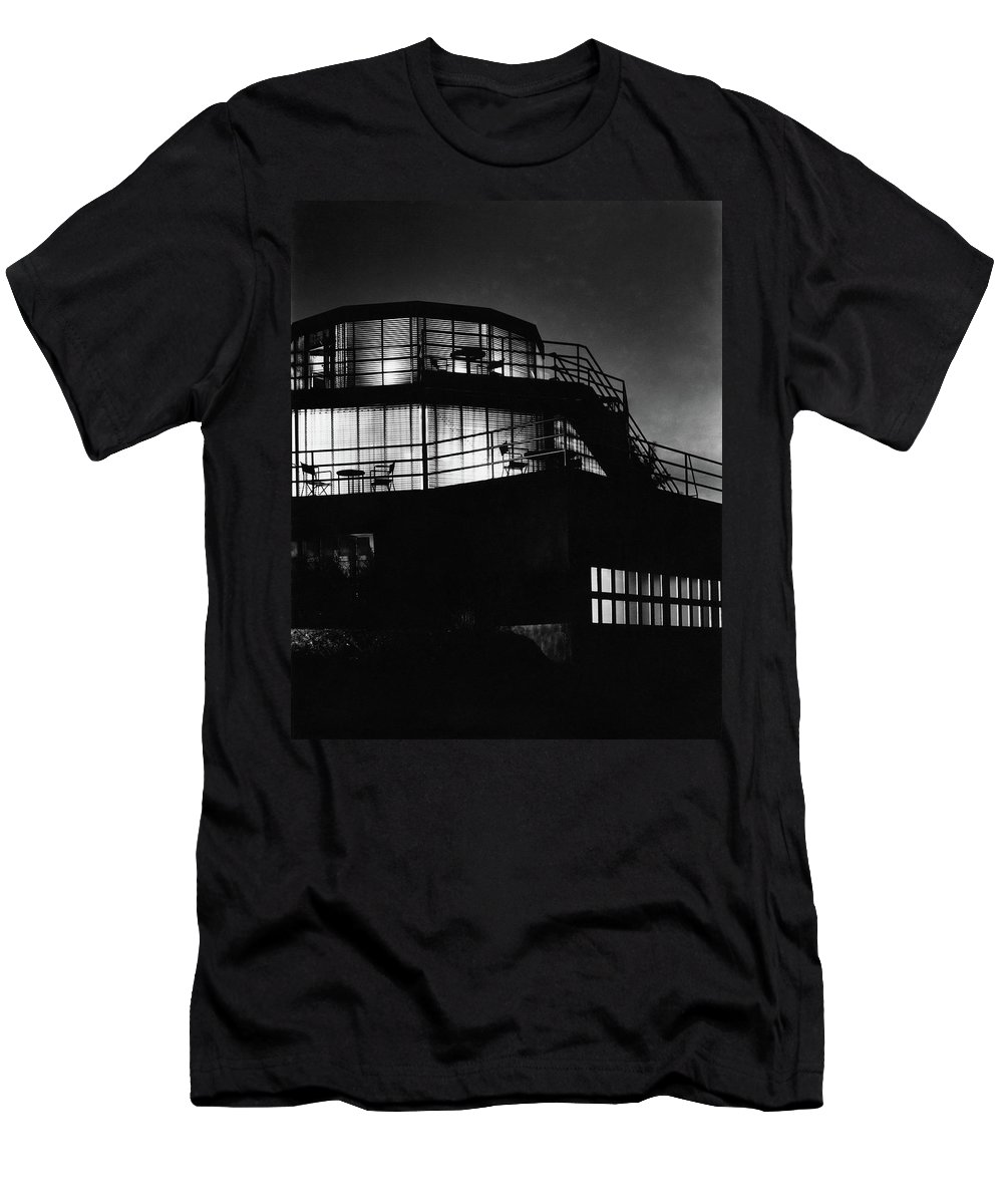Home Men's T-Shirt (Athletic Fit) featuring the photograph The Exterior Of A Spiral House Design At Night by Eugene Hutchinson