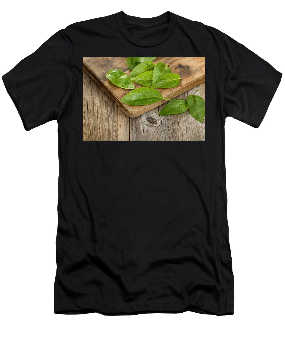 Basil Men's T-Shirt (Athletic Fit) featuring the photograph Close Up Fresh Basil Leafs On Rustic Serving Board by Thomas Baker