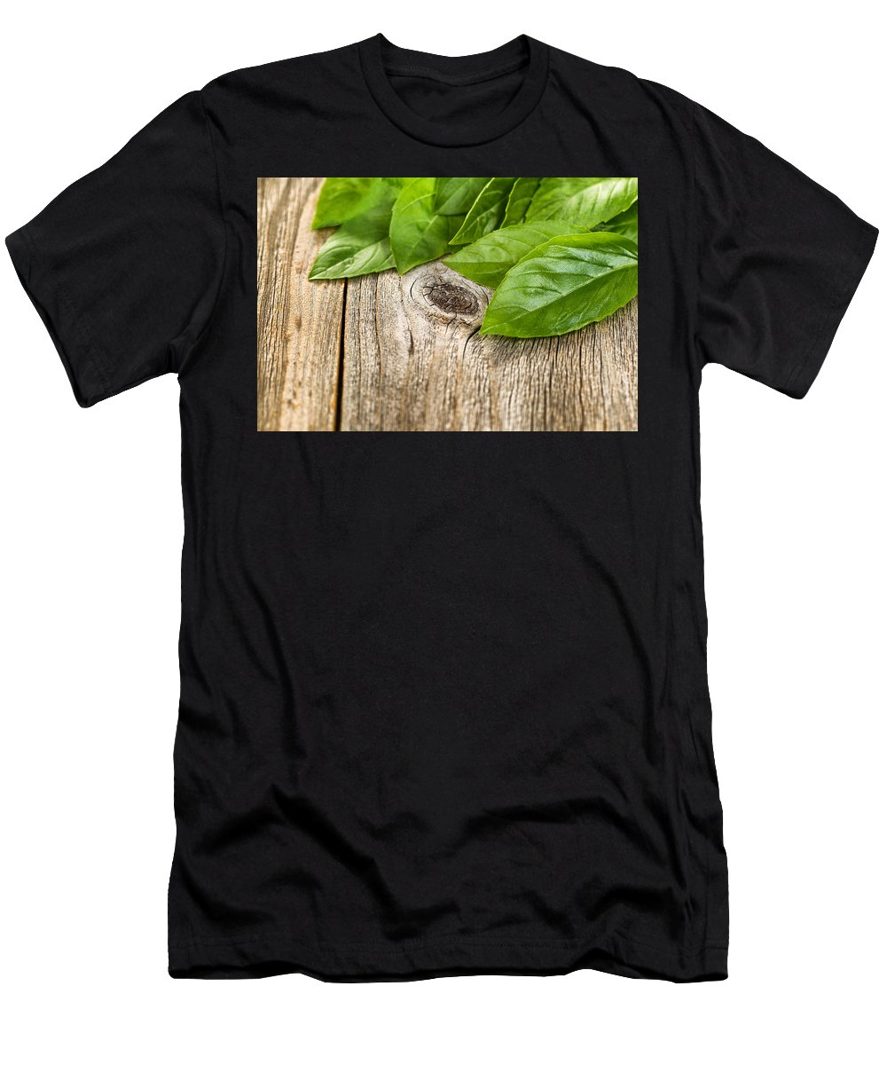 Basil Men's T-Shirt (Athletic Fit) featuring the photograph Close Up Fresh Basil Leafs On Rustic Wooden Boards by Thomas Baker