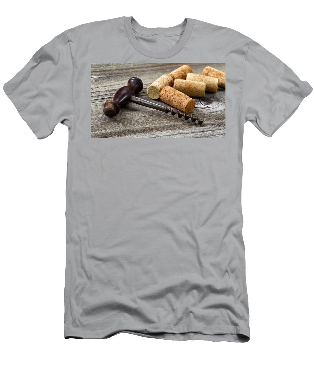 Corkscrew Men's T-Shirt (Athletic Fit) featuring the photograph Old Corkscrew With Used Corks In Background On Aged Wood by Thomas Baker