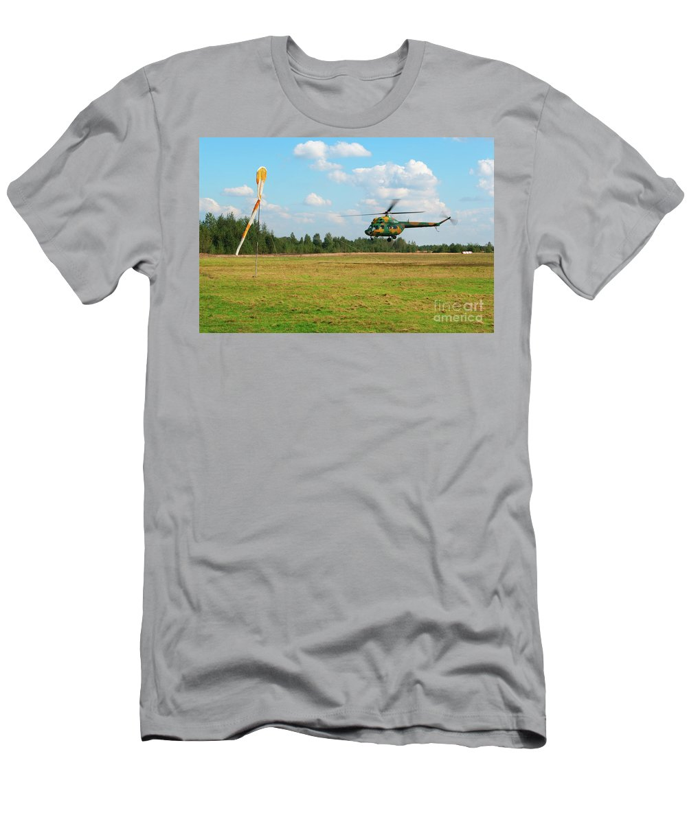 Air Men's T-Shirt (Athletic Fit) featuring the photograph The Helicopter Over A Green Airfield. by Vadzim Kandratsenkau