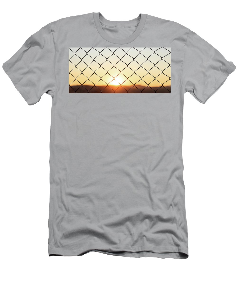 Fence Men's T-Shirt (Athletic Fit) featuring the photograph Wire Mesh Fence On A Sunset Background by George Tsartsianidis