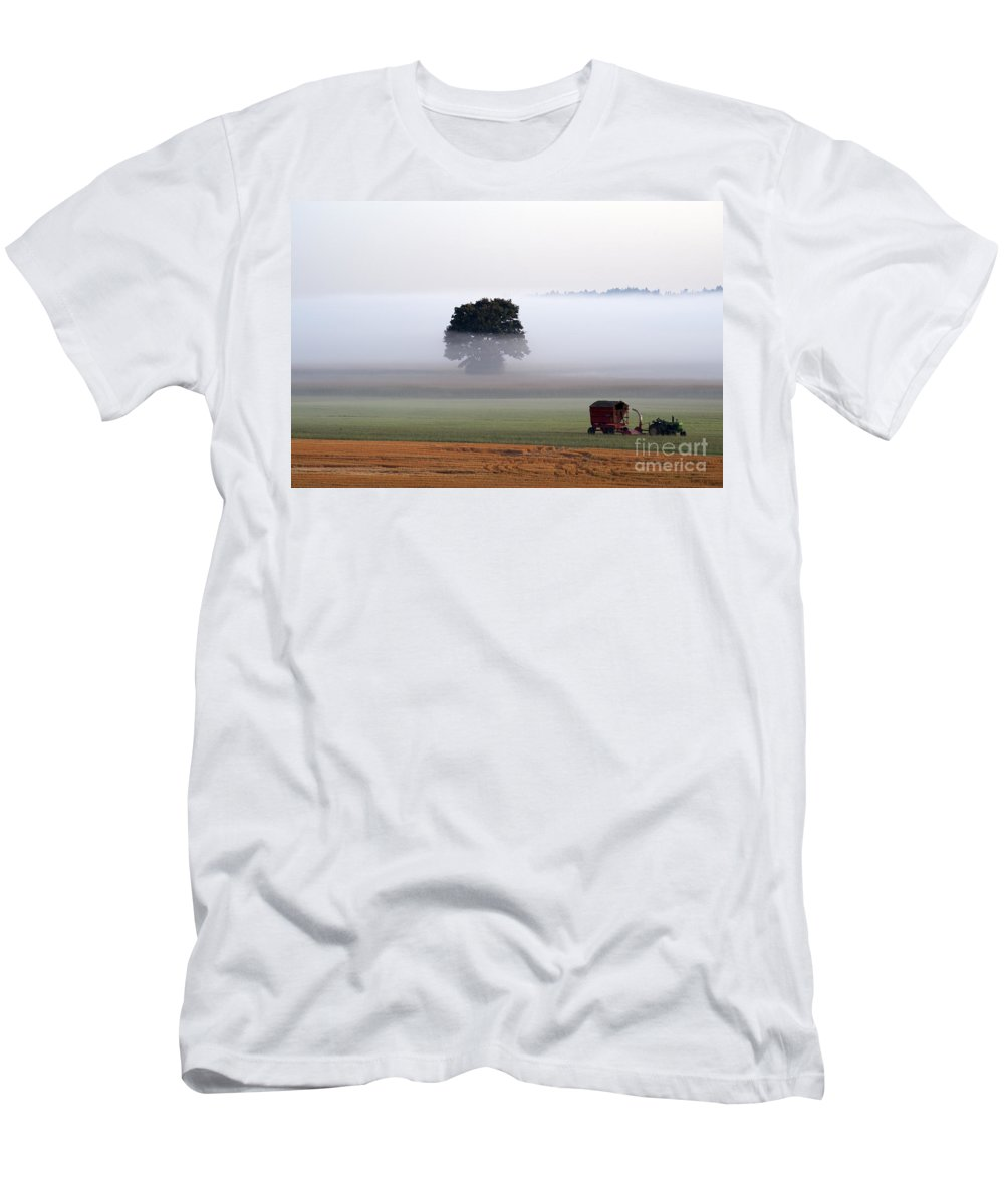 Agriculture Men's T-Shirt (Athletic Fit) featuring the photograph Tractor In Field Low Fog With Tree And Harvester by Jim Corwin