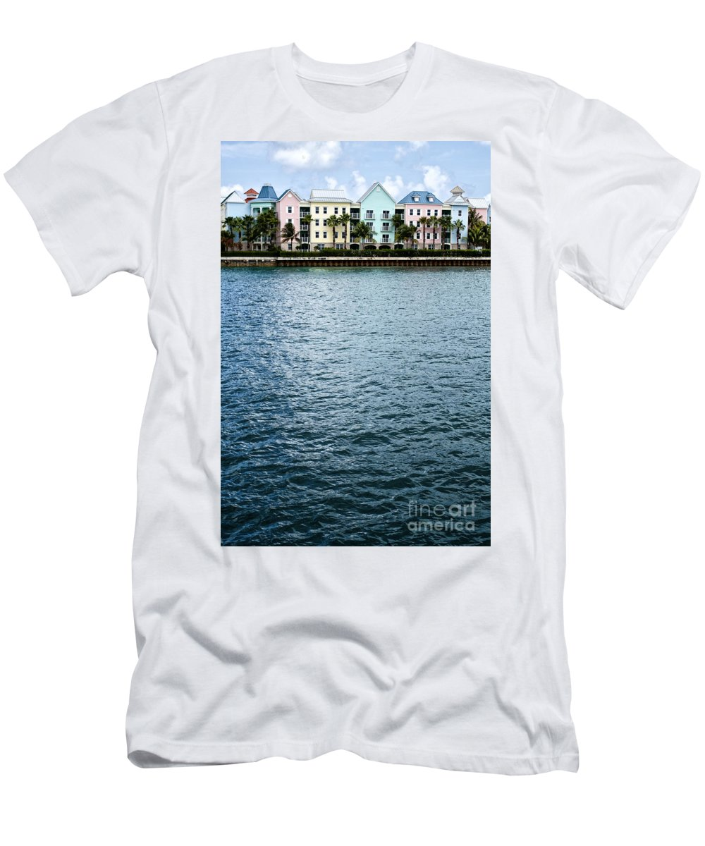 House; Condo; Townhome; Water; Shallow; Island; Tropical; Shore; Waterfront; Bahamas; Blue; Sky; Clouds; Trees; Buildings; Colors; Colorful; Pink; Yellow; Green; Festive; Palm Trees; Outside; Outdoors; Exterior; Home; Tropics; Row Men's T-Shirt (Athletic Fit) featuring the photograph Waterfront Colors by Margie Hurwich