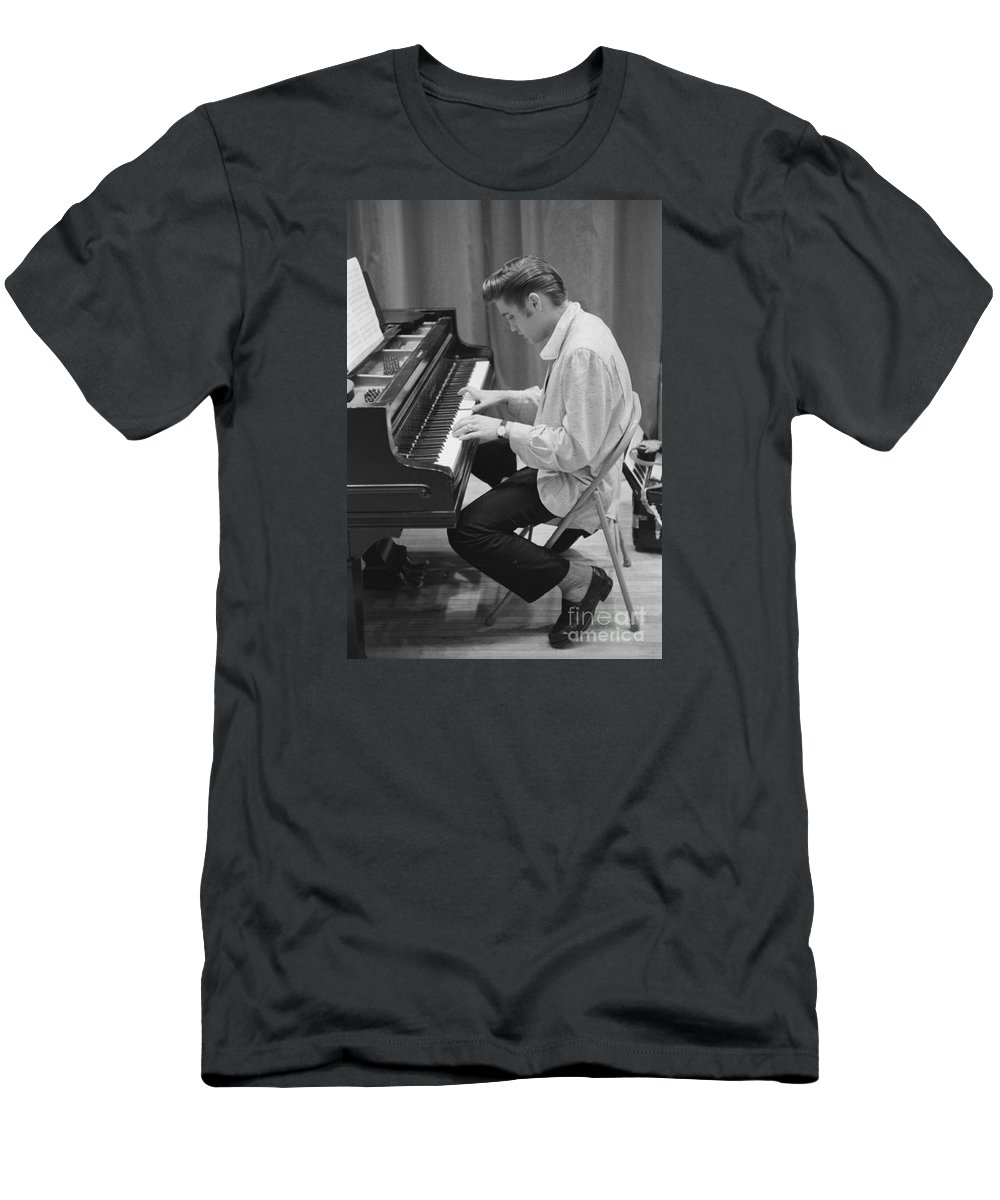 Elvis Presley T-Shirt featuring the photograph Elvis Presley on piano while waiting for a show to start 1956 by The Harrington Collection