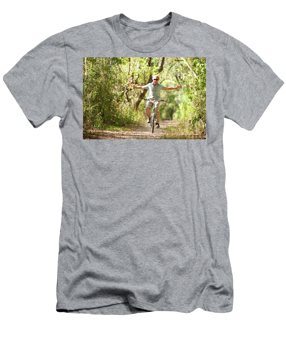 30-34 Years Men's T-Shirt (Athletic Fit) featuring the photograph A Man Rides A Bicycle by Corey Rich