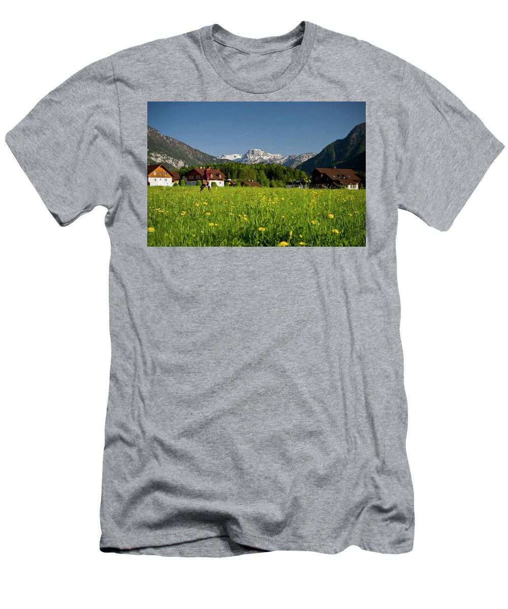 Austria Men's T-Shirt (Athletic Fit) featuring the photograph A Woman Walks Through An Alpine Meadow by Robert van Waarden