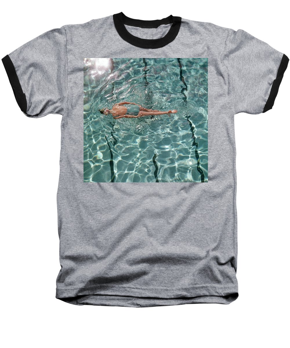 Water Baseball T-Shirt featuring the photograph A Woman Swimming In A Pool by Fred Lyon