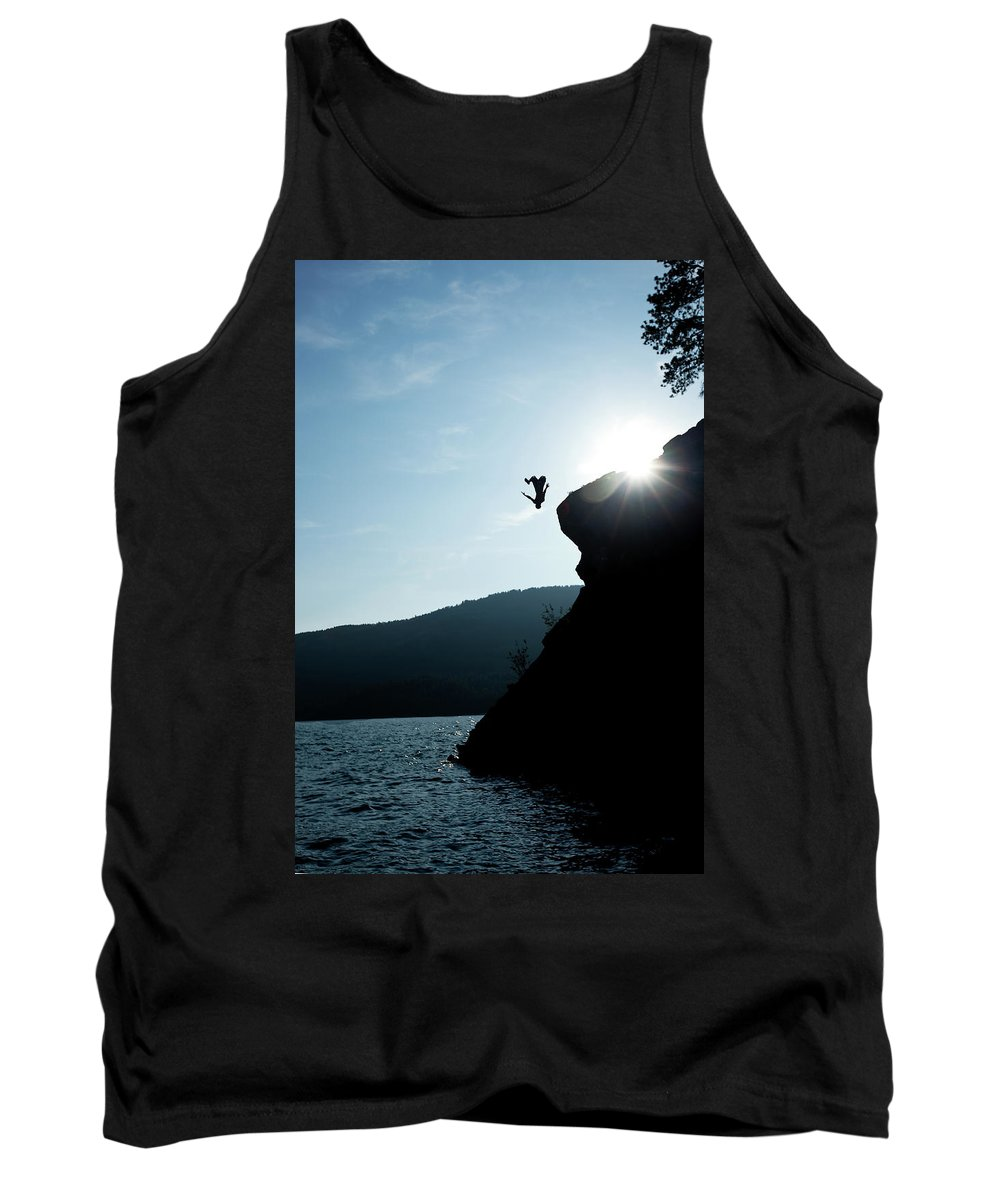 Back Lit Tank Top featuring the photograph A Young Man Flips Off A Rock by Patrick Orton