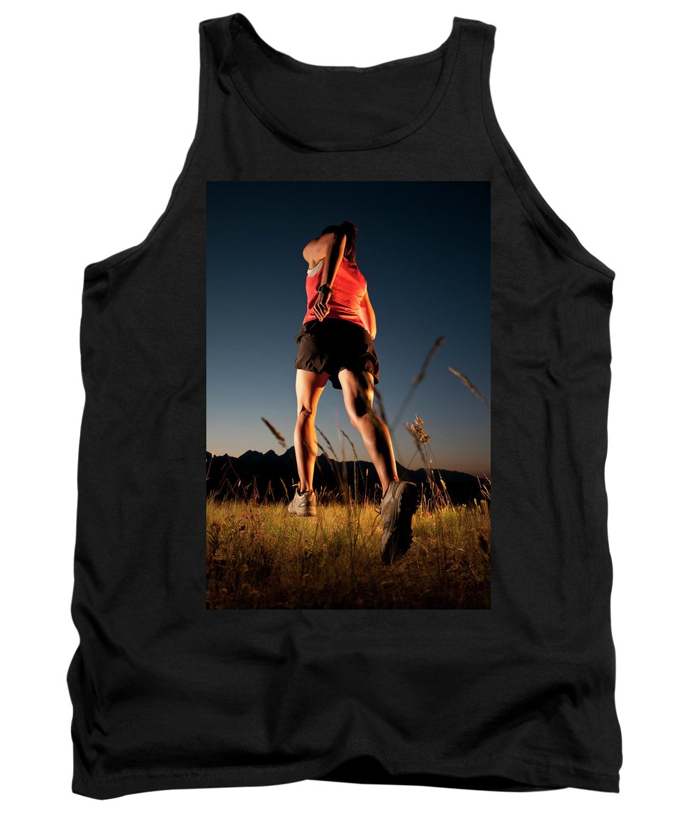 30-34 Years Tank Top featuring the photograph A Young Woman Runs Through A Grassy by Jeff Diener