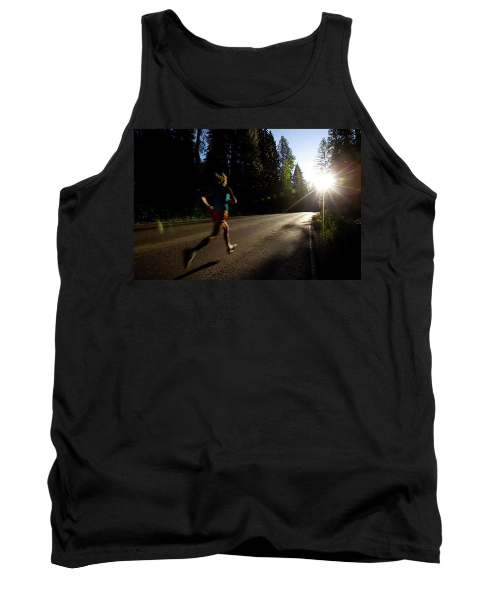 Athlete Tank Top featuring the photograph A Woman Running On A Country Road by Woods Wheatcroft
