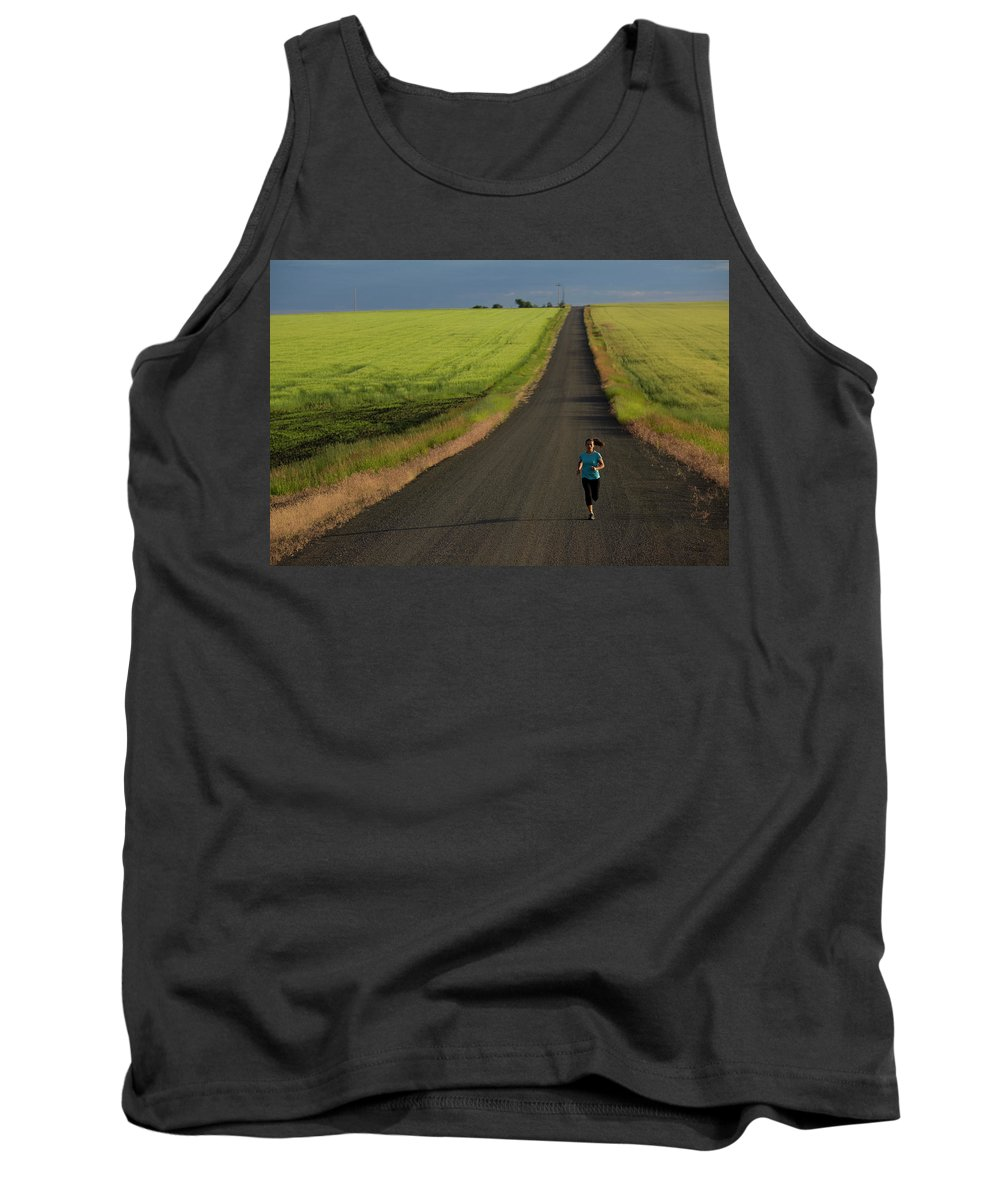 40-44 Years Tank Top featuring the photograph A Woman Running On A Dirt Road by Woods Wheatcroft