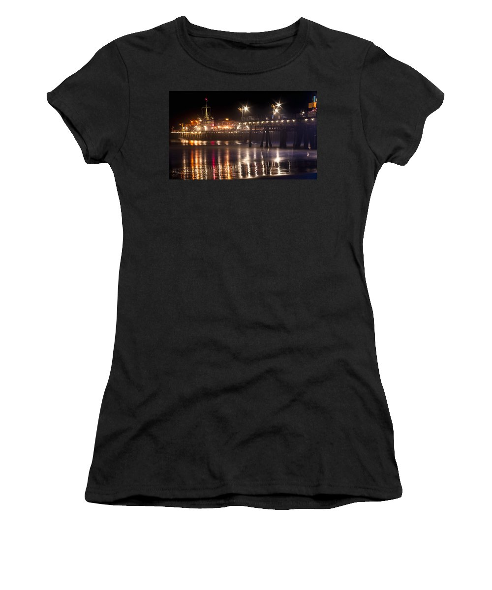 Night Santa Monica Beach Pier Prints Women's T-Shirt (Athletic Fit) featuring the photograph Night On Santa Monica Beach Pier With Bright Colorful Lights Reflecting On The Ocean And Sand Fine A by Jerry Cowart