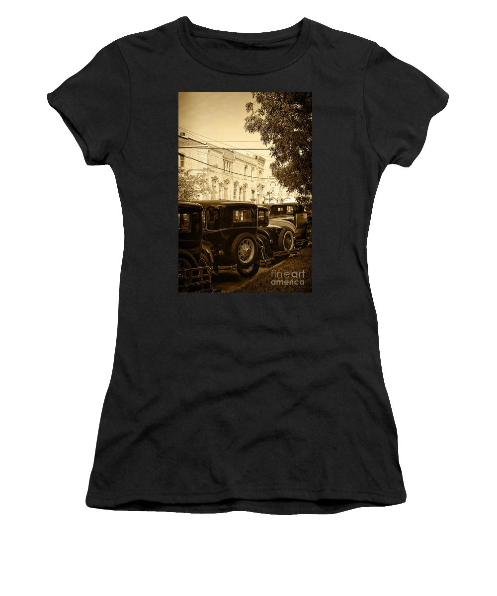 Model A; Vintage; Antique; Buildings; Wires; Trees; Street; City; Town; Parked; Back; Tires; Flags; Lights; Electricity; Sepia; Cars; Autos; Automobiles; Transportation; Turn Of The Century; Early 1900s; 20s; 1920s; Ford; Road; Vehicle Women's T-Shirt featuring the photograph Parked Model A's by Margie Hurwich