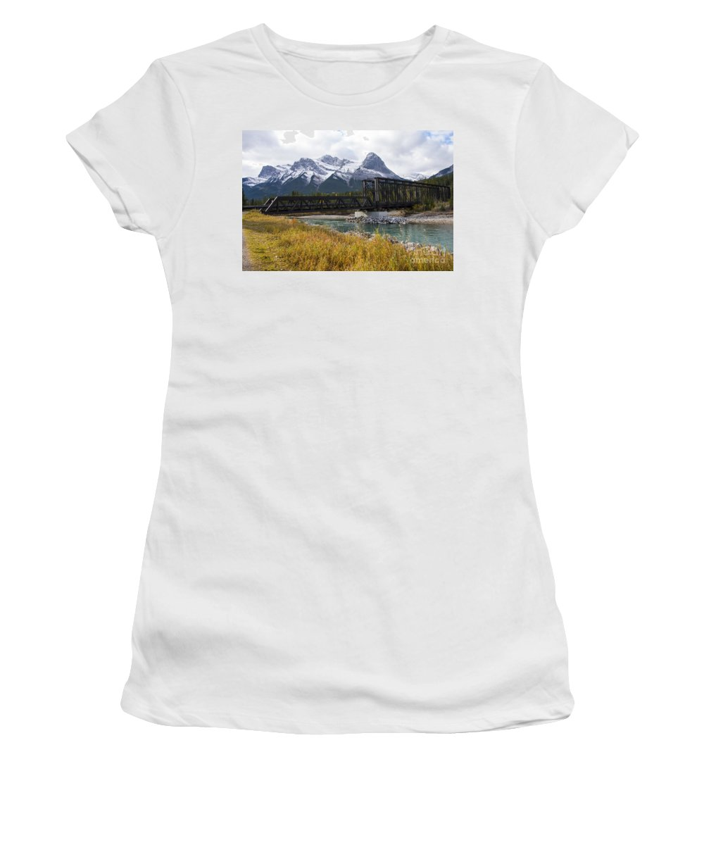 Canmore Canada Iron Bridge Railroad Bridges Trestle Trestles Mountain Rocky Mountains Cloud Clouds Grass Grasses Bow River Rivers Canadian Rockies Snow Peak Peaks Rock Rocks Stone Stones Women's T-Shirt (Athletic Fit) featuring the photograph Bow River Railroad Trestle by Bob Phillips