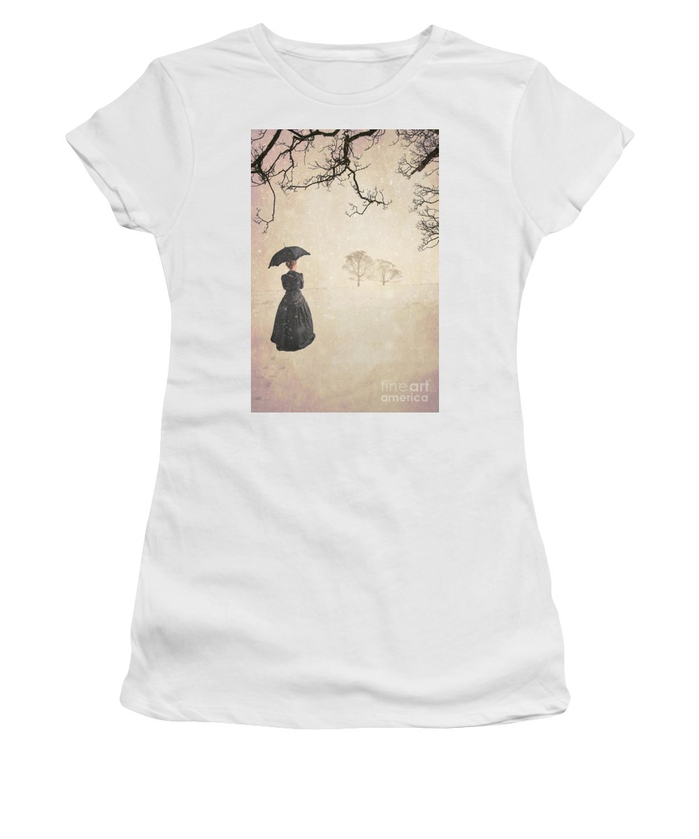 Victorian; Historical; Woman; Female; Dress; Parasol; Standing; Walking; Waiting; Rear View; Back; From Behind; Anonymous; Outdoors; Outside; Era; Period; Vintage; Snow; Snowy; Snowing; Cold; Winter; Mourning; Black; Widow; Landscape; Tree; Trees; Horizon; Atmospheric Women's T-Shirt featuring the photograph Victorian Woman In Winter by Lee Avison