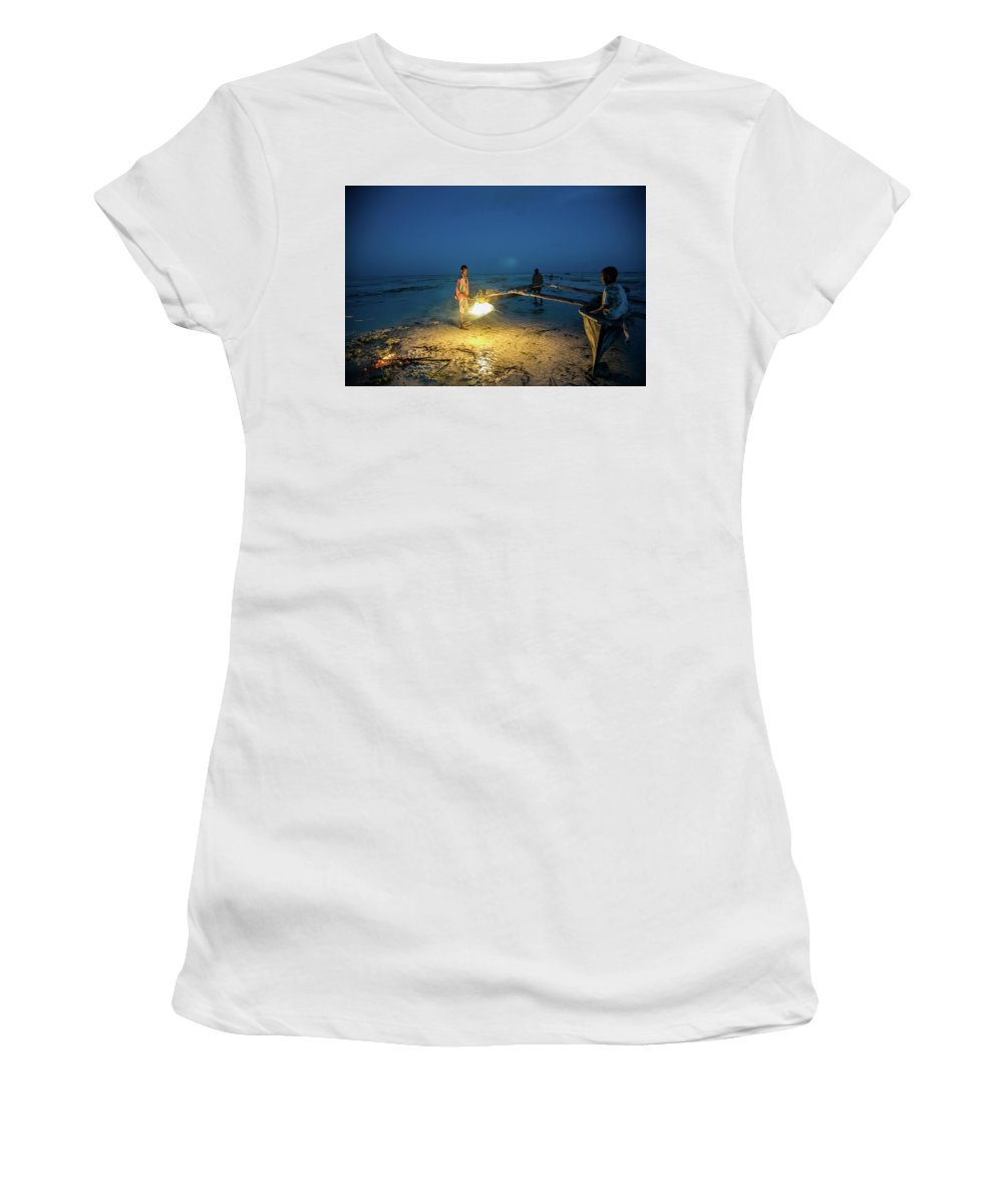 Tanzania Women's T-Shirt (Athletic Fit) featuring the photograph A Local Fisherman Uses Flame To Repair His Boat At Sunset by Gareth Pickering