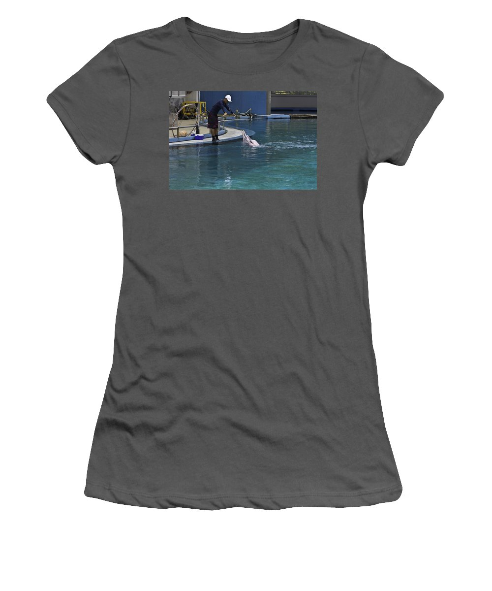 2 Dolphins Women's T-Shirt (Athletic Fit) featuring the photograph Trainer Feeding Duo Of Dolphins At The Underwater World In Sentosa by Ashish Agarwal