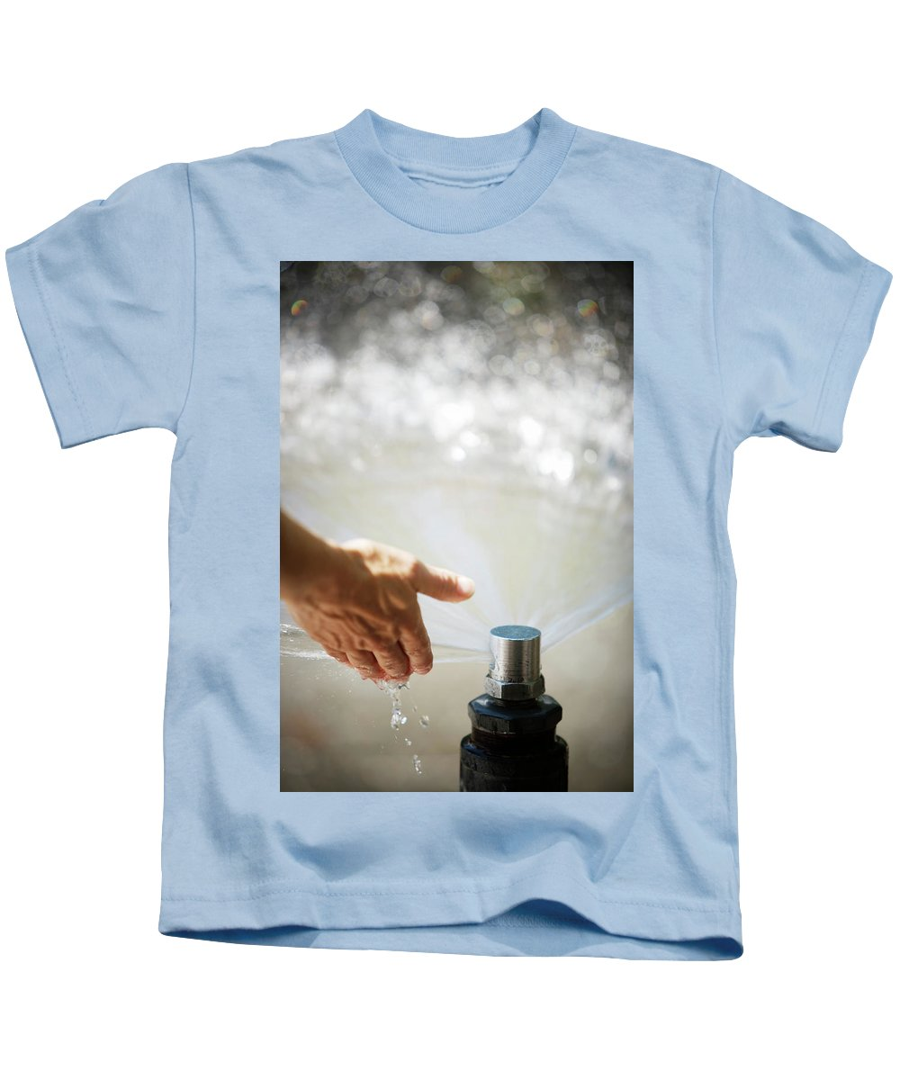 Cold Kids T-Shirt featuring the photograph A Hand In A Playground Sprinkler by Ron Koeberer