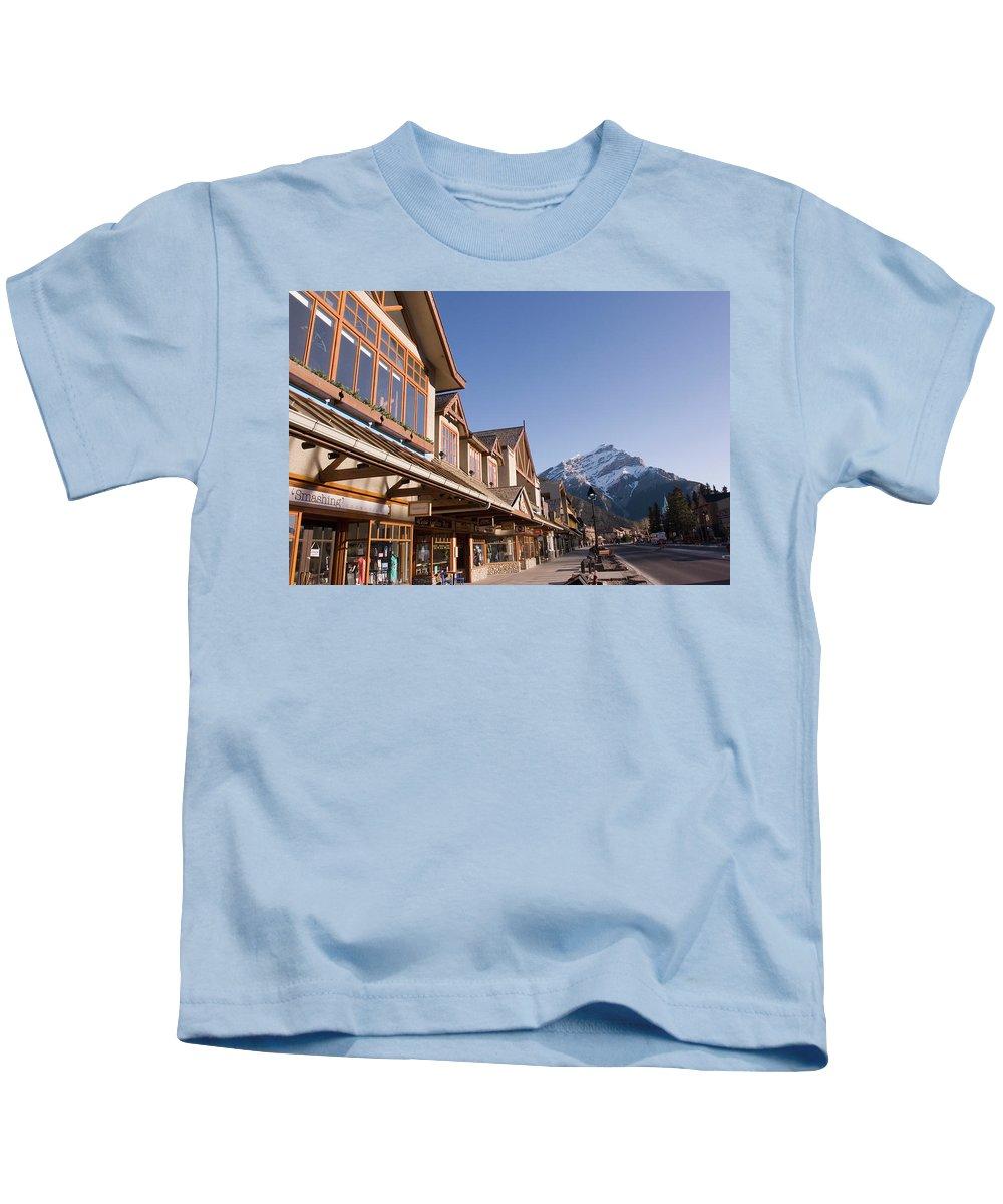 Alberta Kids T-Shirt featuring the photograph Banffs Main Street Banff Avenue At Dawn by Dan Shugar