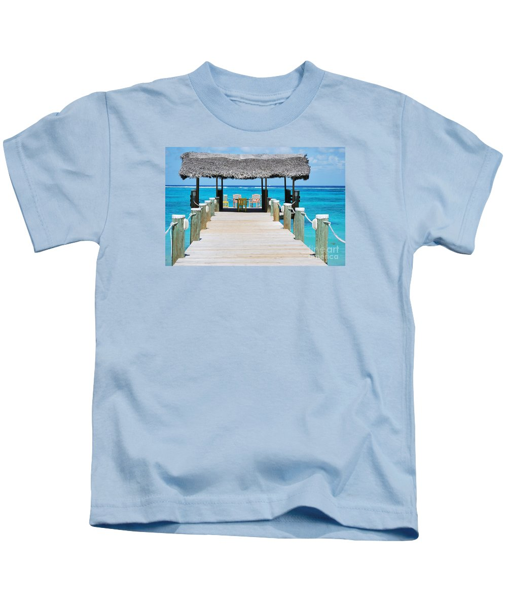 Bahamas Art Caribbean Compass Point Ocean Travel Serene Stock Shot Seascape Turquoise Water Meditation Thatched Roof Whimsy Jetty Wood Print Metal Frame Canvas Print Poster Print Available On T Shirts Tote Bags Duvet Covers Throw Pillows Shower Curtains Greeting Cards Mugs Pouches Weekender Tote Bags Beach Towels And Phone Cases Kids T-Shirt featuring the photograph Tranquility At Compass Point, Nassau, Bahamas by Marcus Dagan