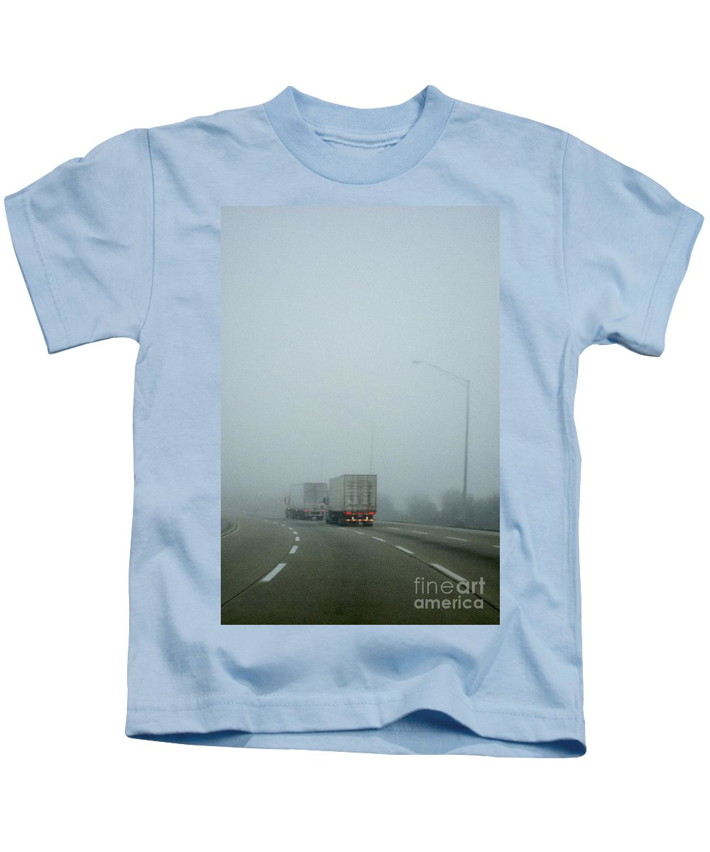Road; Roadway; Highway; Interstate; Lanes; Day; Daytime; Lines; Fog; Foggy; Black; Asphalt; Cement; Shroud; Truck; Semi; Trailer; Transportation; Transport; Two; Back; Taillights; Lights; Curve; Bend; Street Lights Kids T-Shirt featuring the photograph Semis by Margie Hurwich
