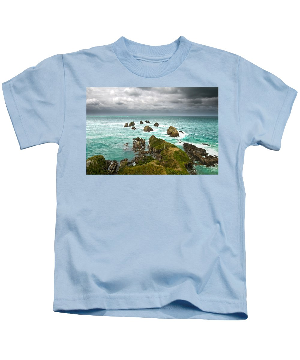Background Kids T-Shirt featuring the photograph Cliffs Under Thunder Clouds And Turquoise Ocean by U Schade