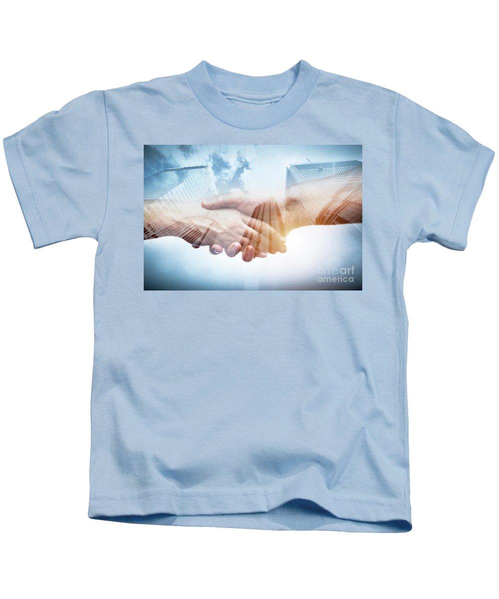 Handshake Kids T-Shirt featuring the photograph Business Handshake Over Modern Skyscrapers, Double Exposure. by Michal Bednarek