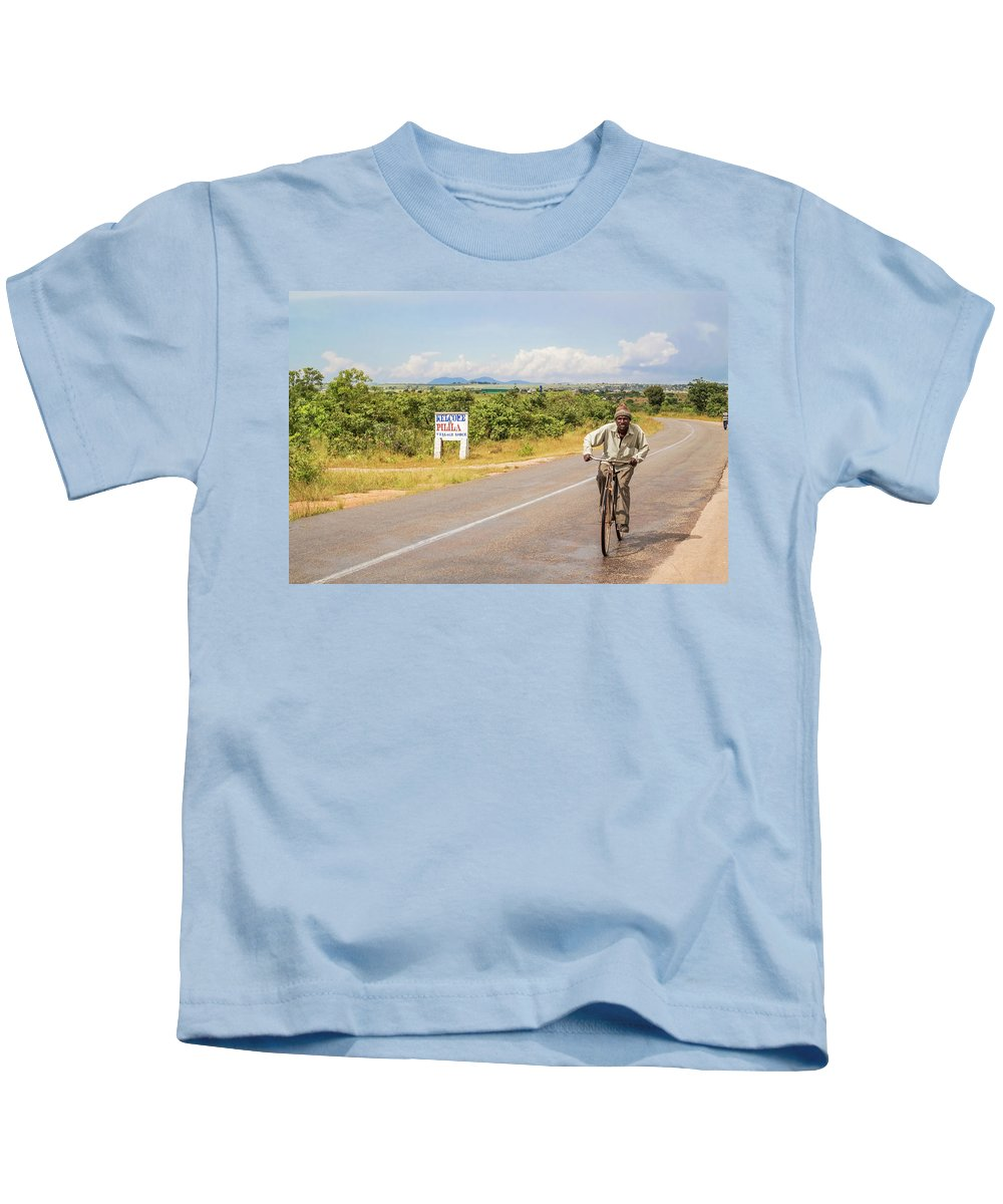 Man Kids T-Shirt featuring the photograph Man On Bicycle In Zambia by Marek Poplawski