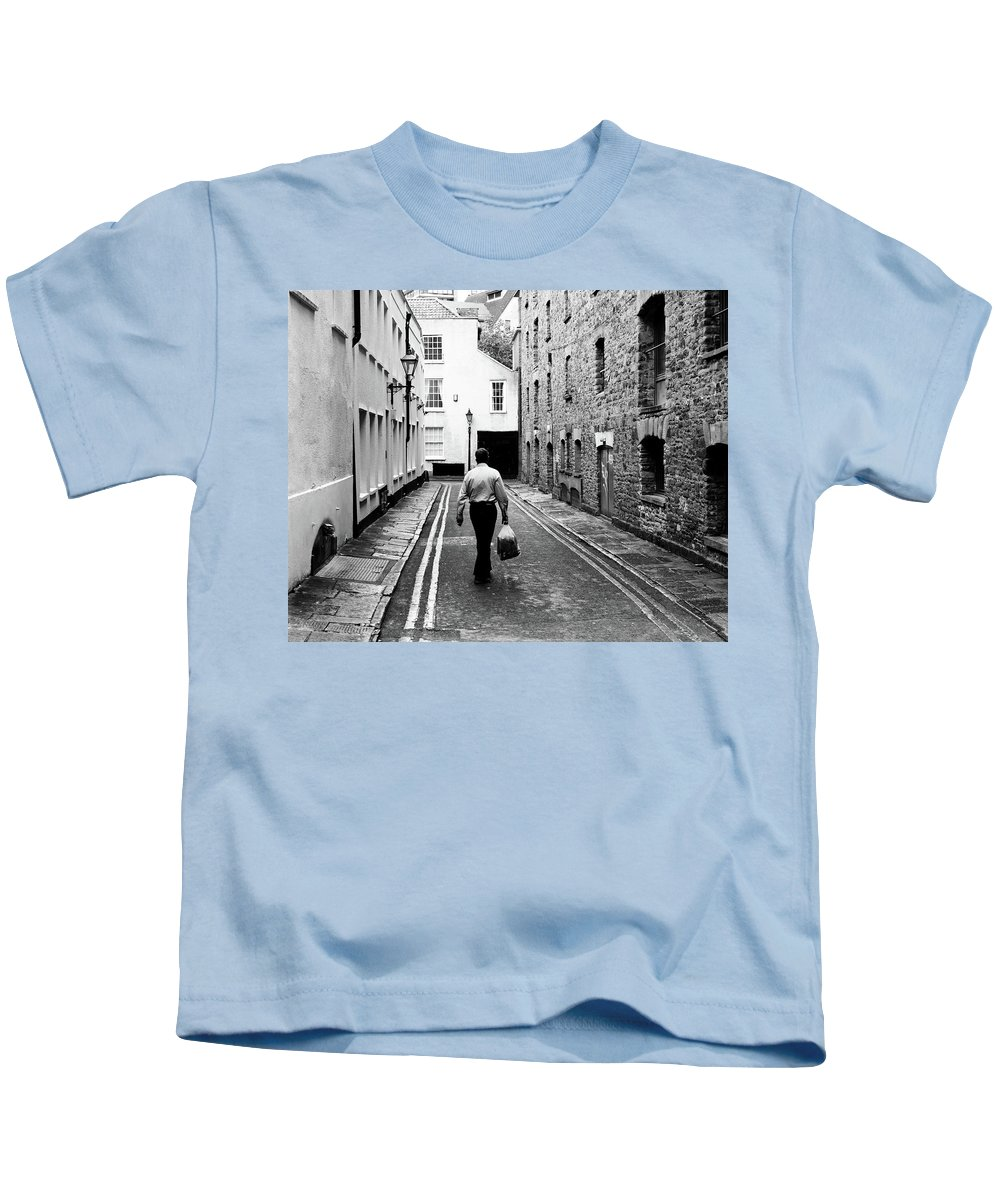 Architecture Kids T-Shirt featuring the photograph Man Walking With Shopping Bag Down Narrow English Street by Jacek Wojnarowski