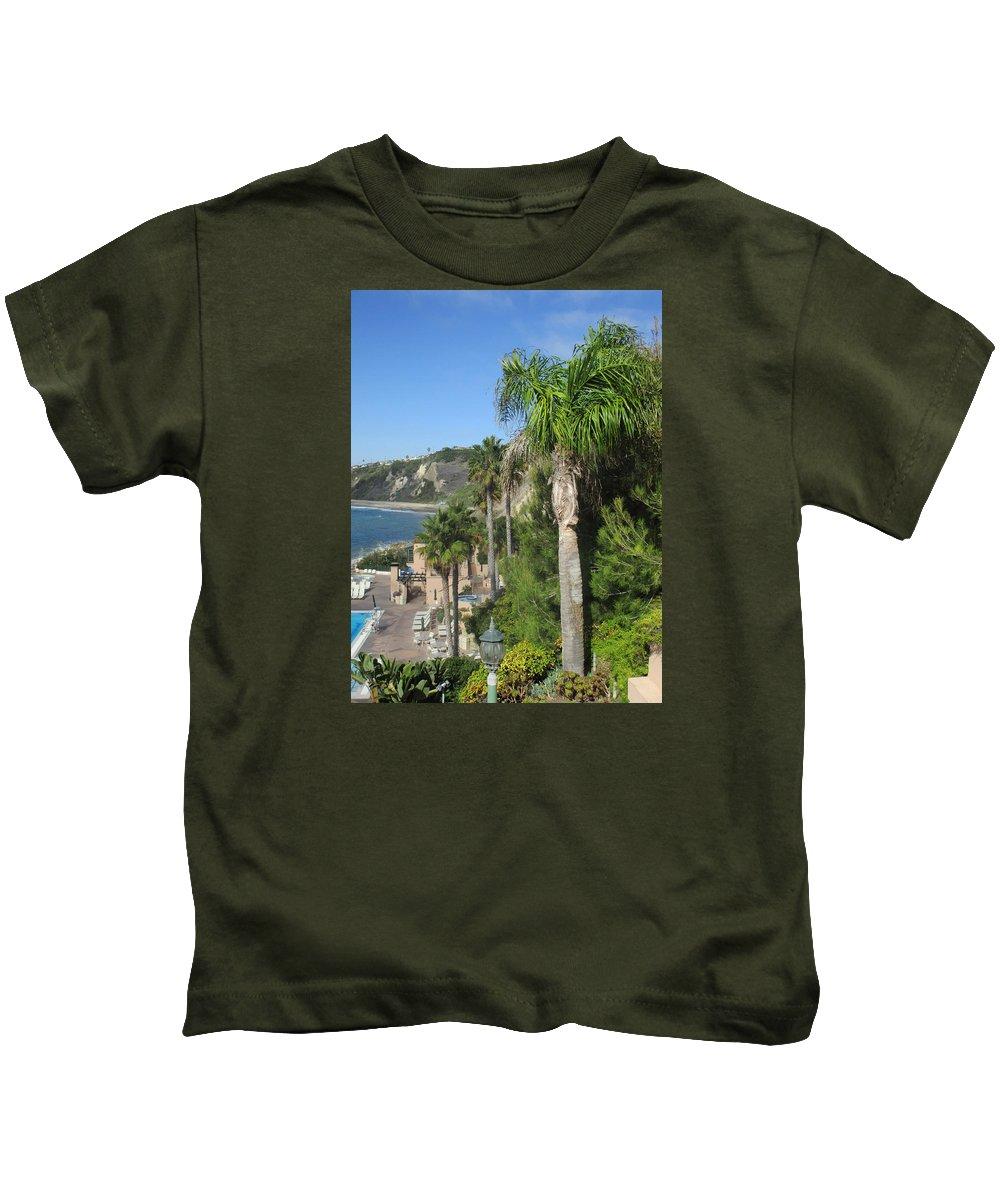 Palm Tree Beach Water Shoreline Sea Ocean Sand Cliffs Plants Landscape Vacation Relaxing Sunbath Pool Swim Surf Waves Kids T-Shirt featuring the photograph Giant Palm by Vivien Rhyan