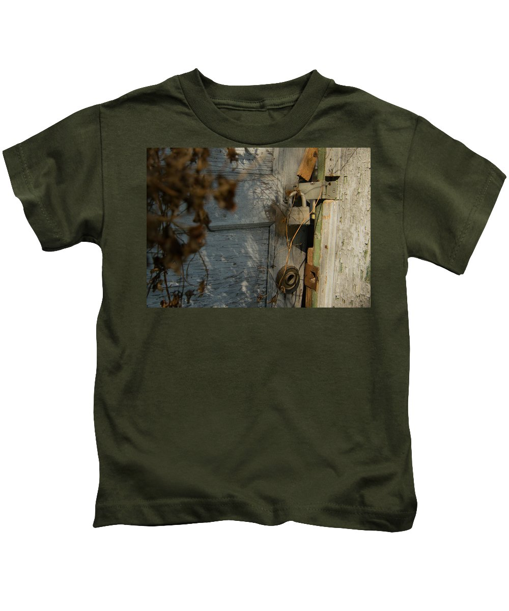 Vanishing Texas Kids T-Shirt featuring the photograph padlocked old wood door abandoned Streetman Texas by Trace Ready